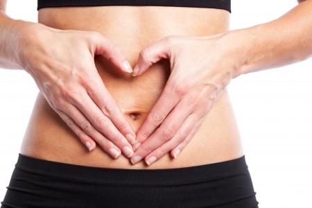 An-isolated-shot-of-a-woman-making-a-heart-sign-on-her-tummy