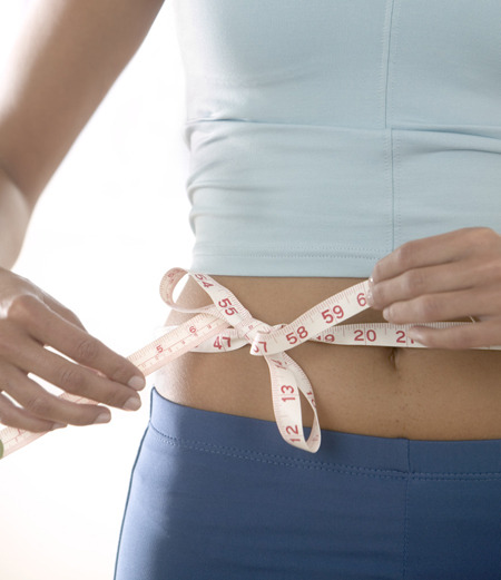 Woman Tying Measuring Tape Around Her Waist